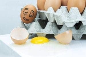 An egg falling out of an egg carton