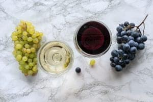 a glass of white wine next to some wine grapes and a glass of red wine next to a bunch of red grapes