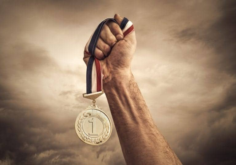 Hand clutching a gold medal