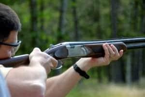 Person aiming laser clay gun