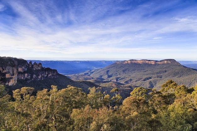 Panorama towards Grand Canyon from Echo point and three sisters rocks formation to central plato above eucalyptus trees on sunny morning.